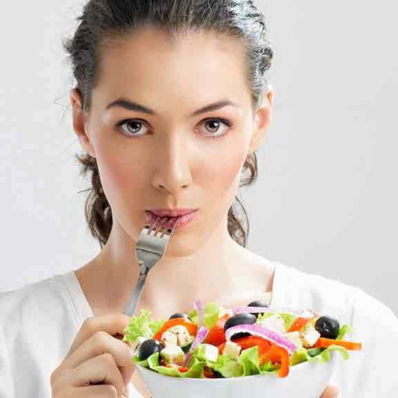 woman with fork in mouth eating salad square