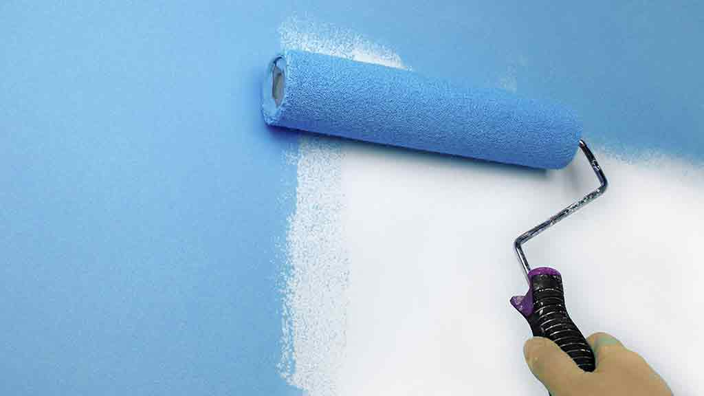 paint roller painting wall blue