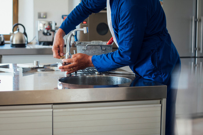 plumber fixing tap at home