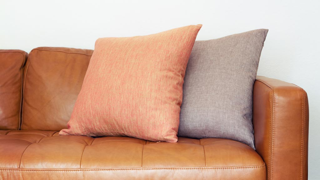 tan leather couch with pillows lead