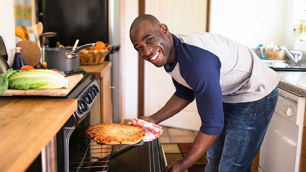 man using oven to cook pizza