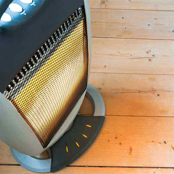Electric heater on wooden floor
