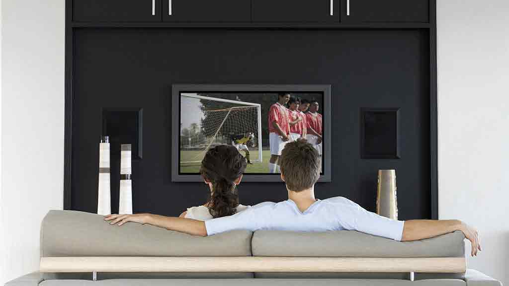 man and woman watch soccer on tv