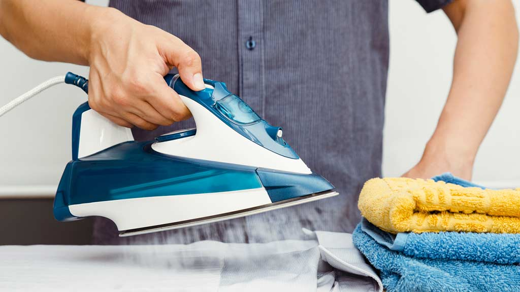 man using iron to do ironing