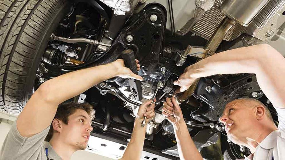 two men fixing a car engine