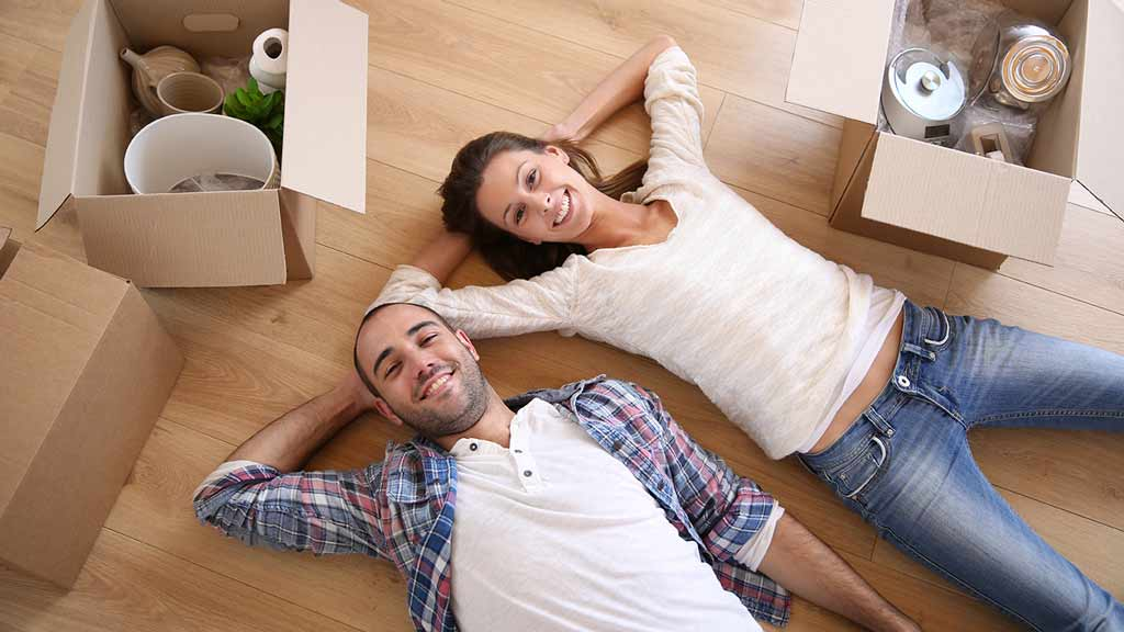 house with a for sale sign two people lying on the floor with boxes