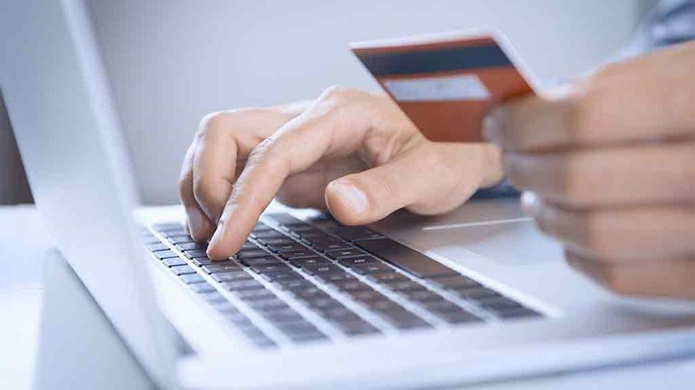 person typing in computer while holding credit card