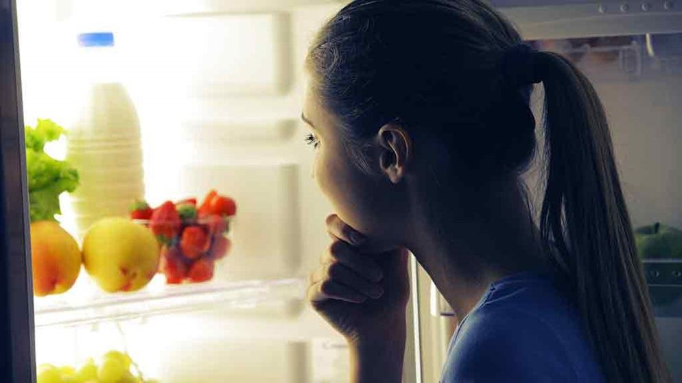 woman looks into open fridge