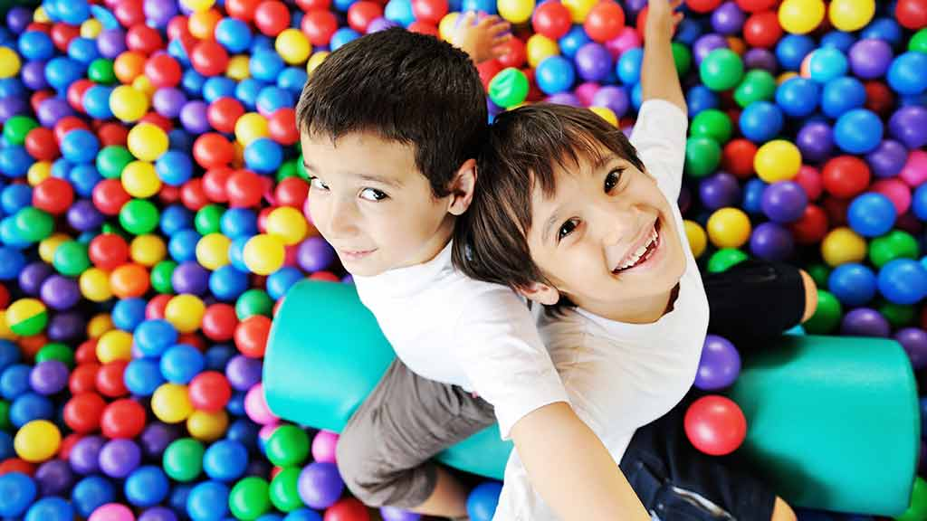 two children in ball pit playing safety