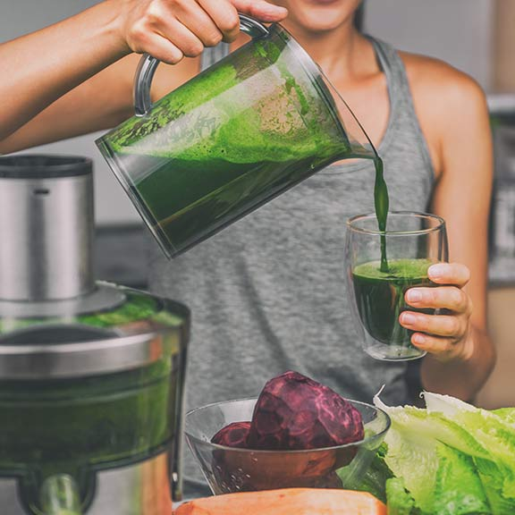 woman using juicer to make green juice sq