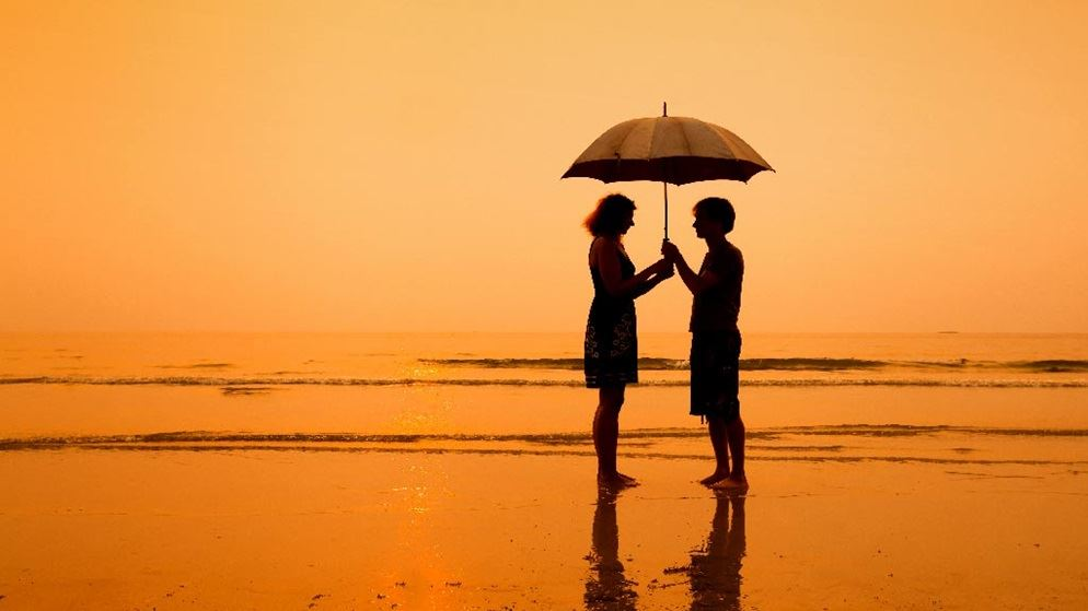 couple on beach holding umbrella at sunset