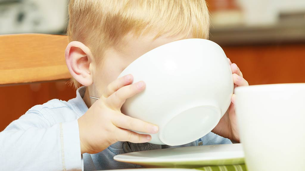 little boy drinking with cereal bowl