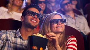 couple watching movie in cinema eating popcorn