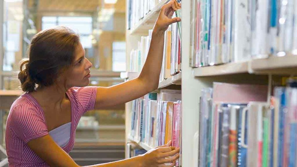 woman looks for book on shelf