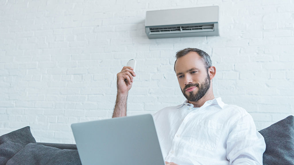 man using air conditioner at home
