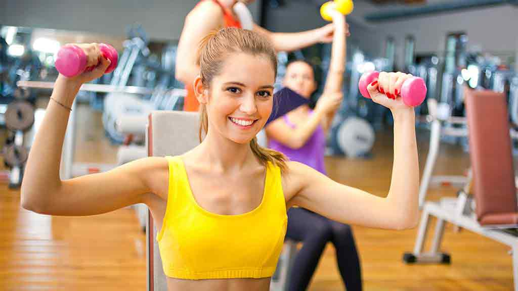 gym and gym membership lady holding weights at gym