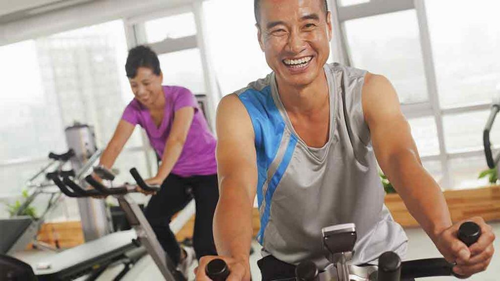 man and woman on exercise bikes at the gym