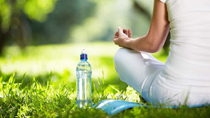 woman sitting meditating with bottle of water