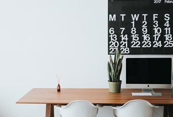 black and white calendar above a brown desk with a computer