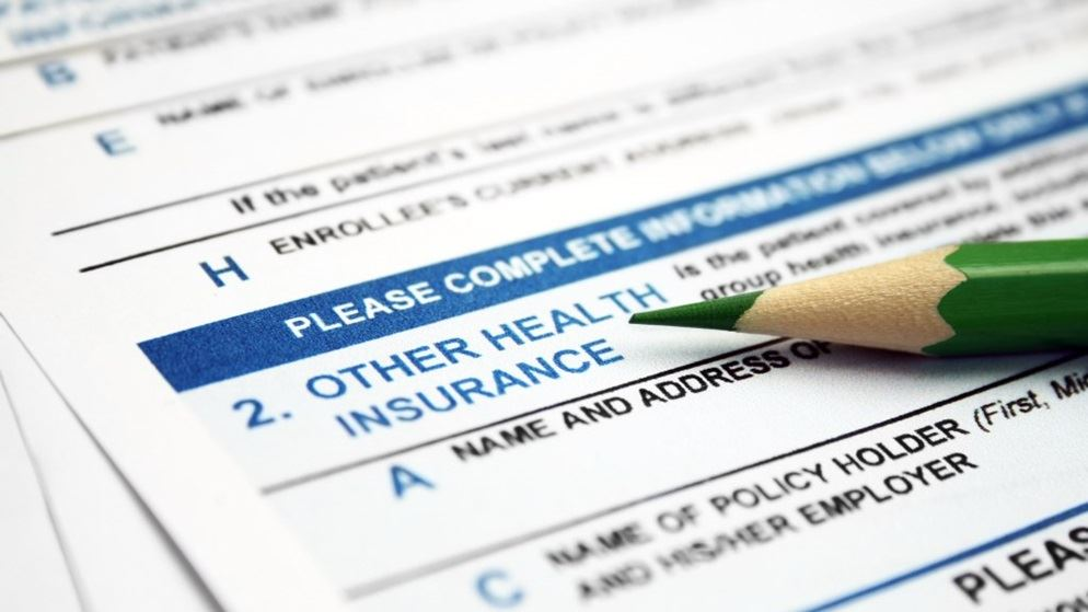 close-up of health insurance form with a green pencil