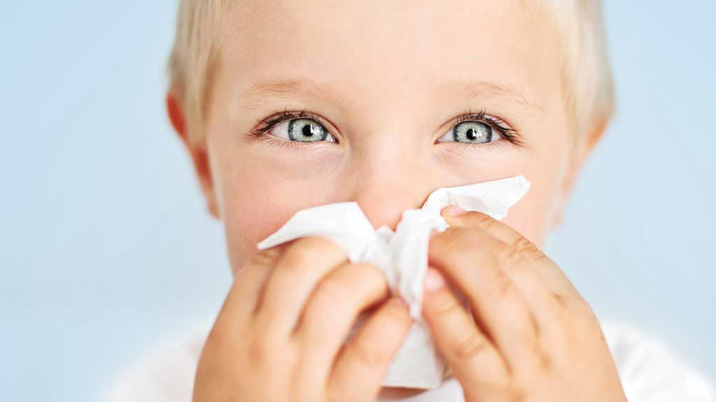 boy wiping nose with wipe