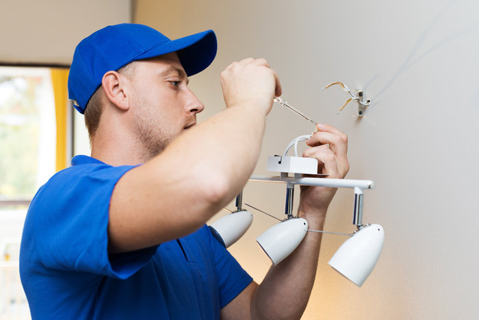 electrician fixing light at home