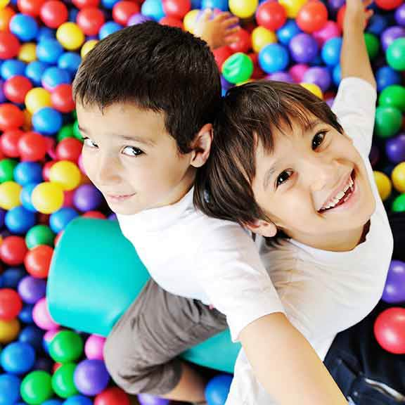 two children in ball pit playing safety sq