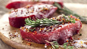 raw meat with herbs on baord
