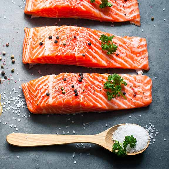 salmon steaks on kitchen board sq