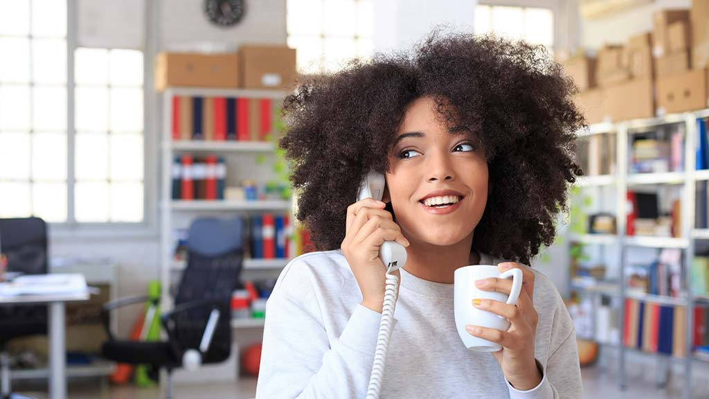 young woman using landline phone
