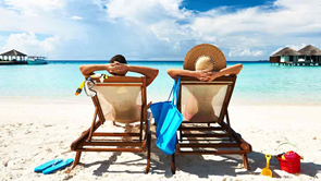 couple relaxing in lounge chairs on a beach