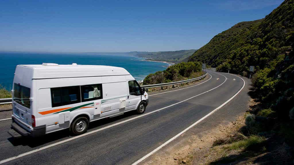 White campervan driving along the Great Ocean Road overlooking the ocean