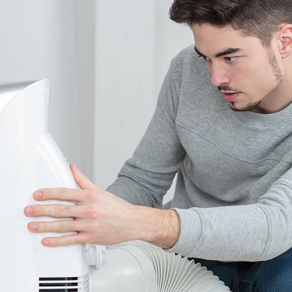 man using a portable air conditioner at home sq