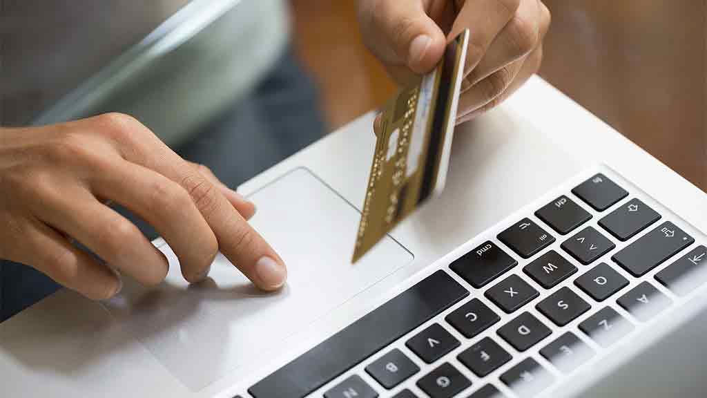 person holds credit card over keyboard