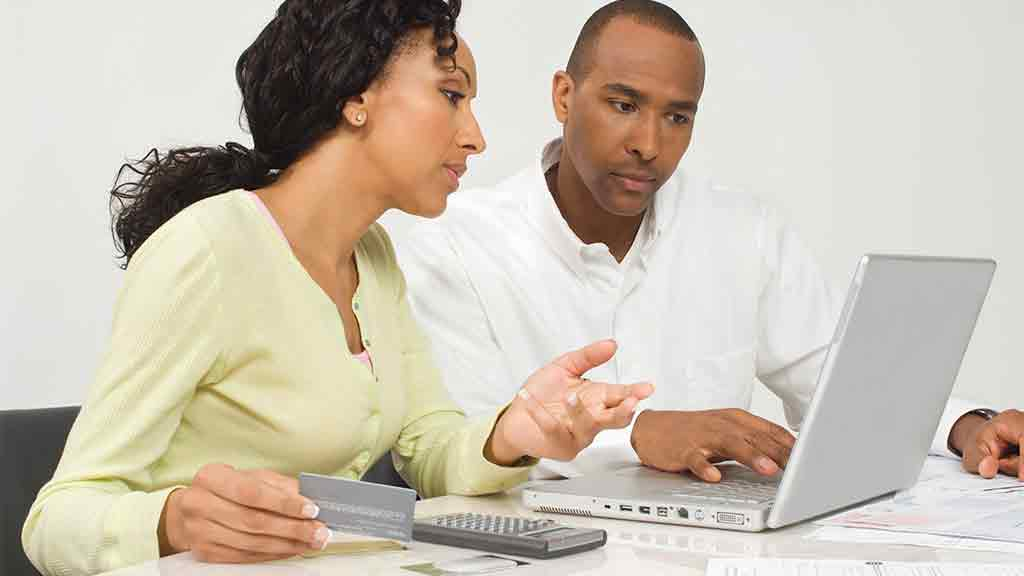 couple looking at laptop and calculator