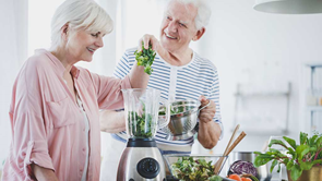 older couple using a blender at home