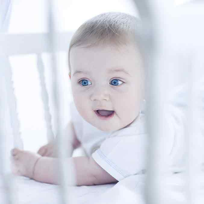 baby looking out of a cot square