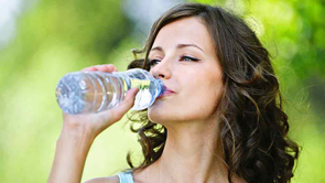 woman drinking water from plastic bottle