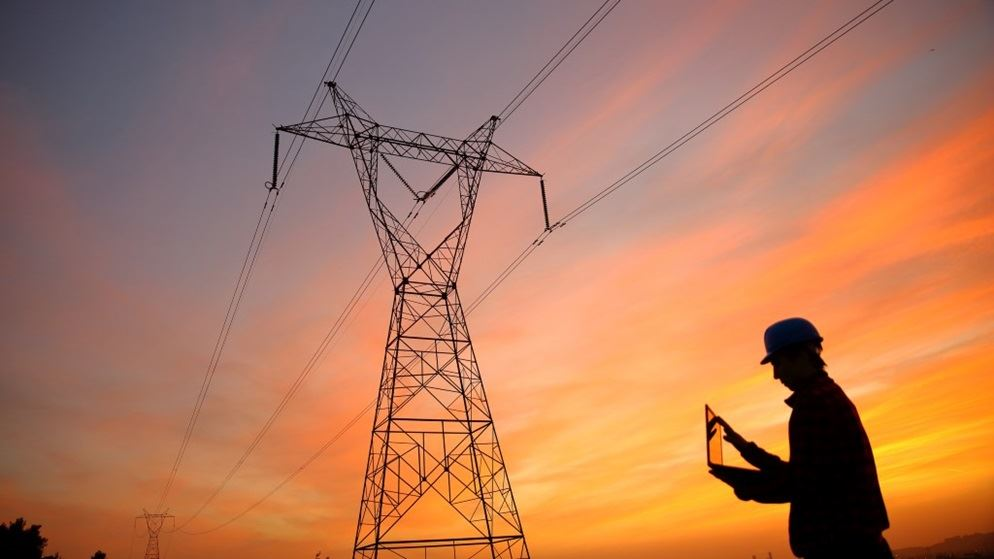 electrical engineer standing near transmission tower