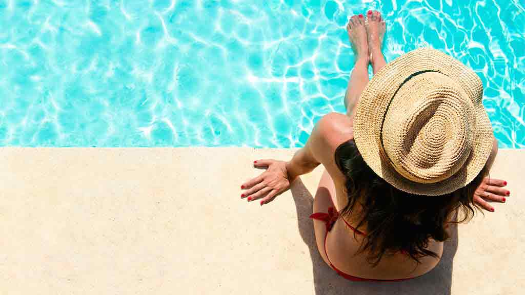 woman sits by pool