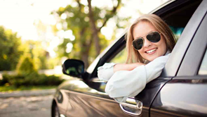 woman in sunglasses looking out car window