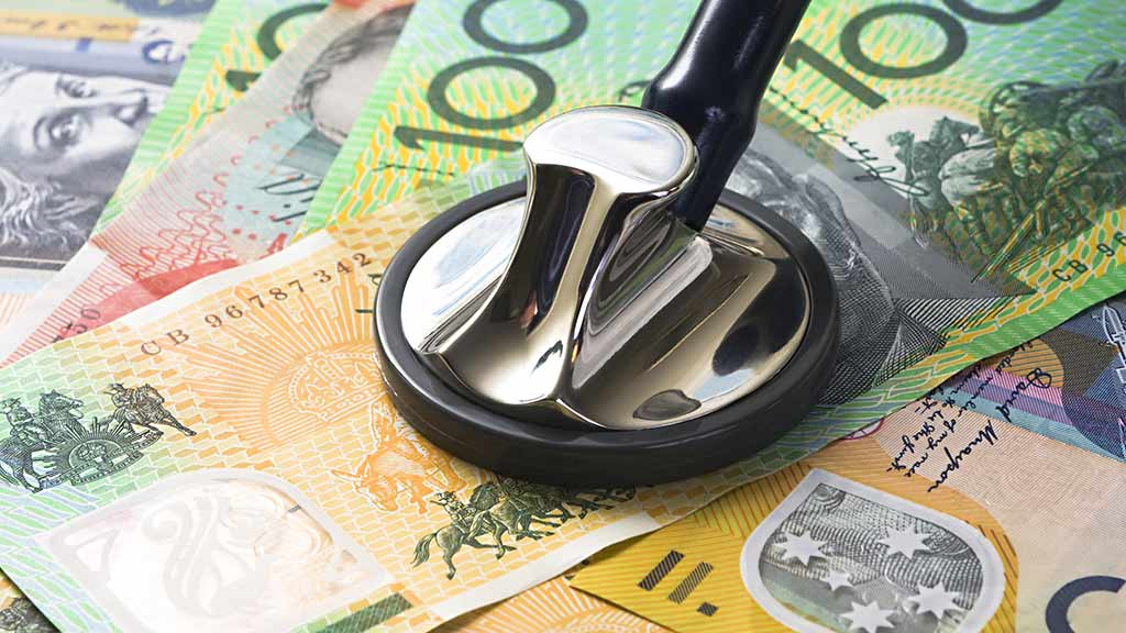 close-up of a stethoscope sitting on Australian money - how to save on health insurance lead image