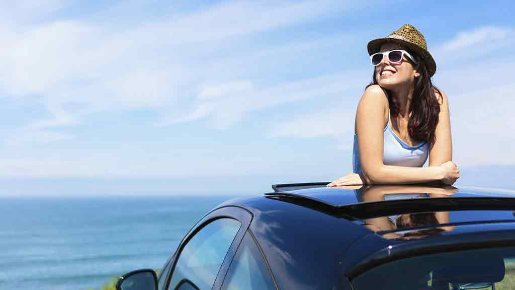 woman pokes head out of car sun roof