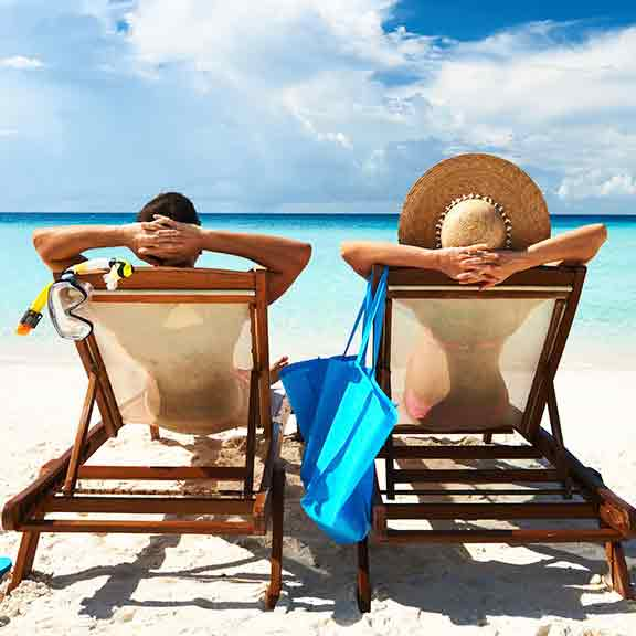 couple relaxing in lounge chairs on a beach square