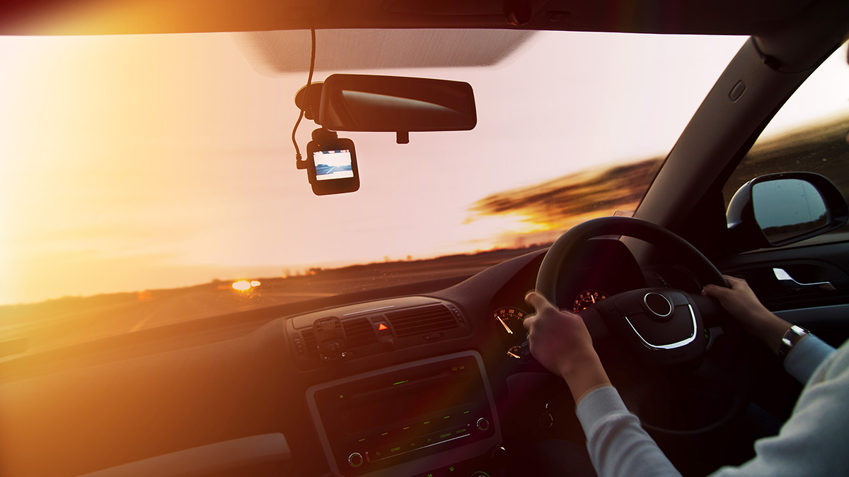 Dash cam below the rear vision mirror on a car window at sunset