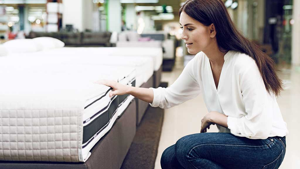 Woman instore looking at and touching a mattress