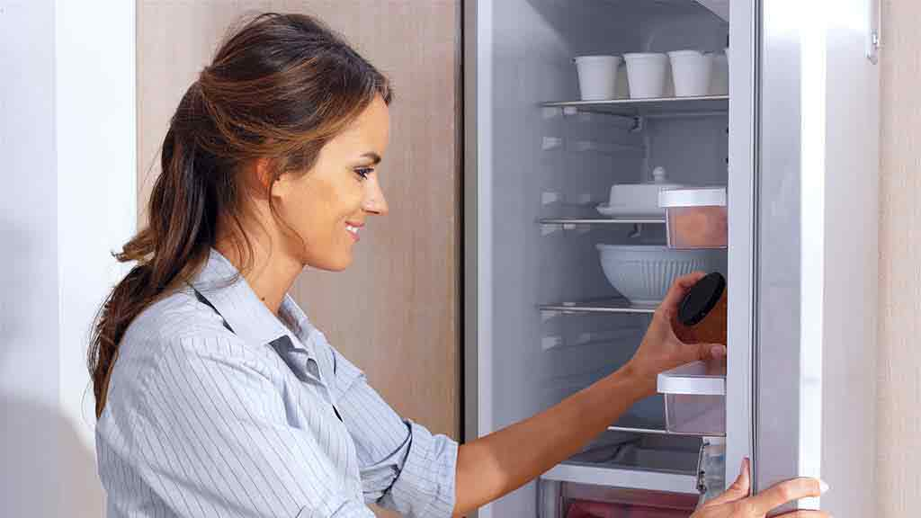 woman opening french door fridge