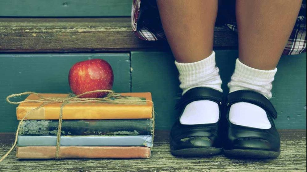closeup_of_school_shoes_with_books_and_apple
