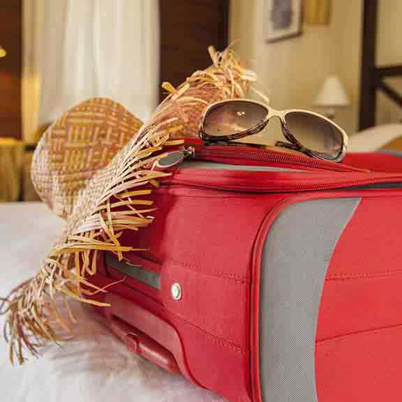 suitcase hat sunglasses on bed square