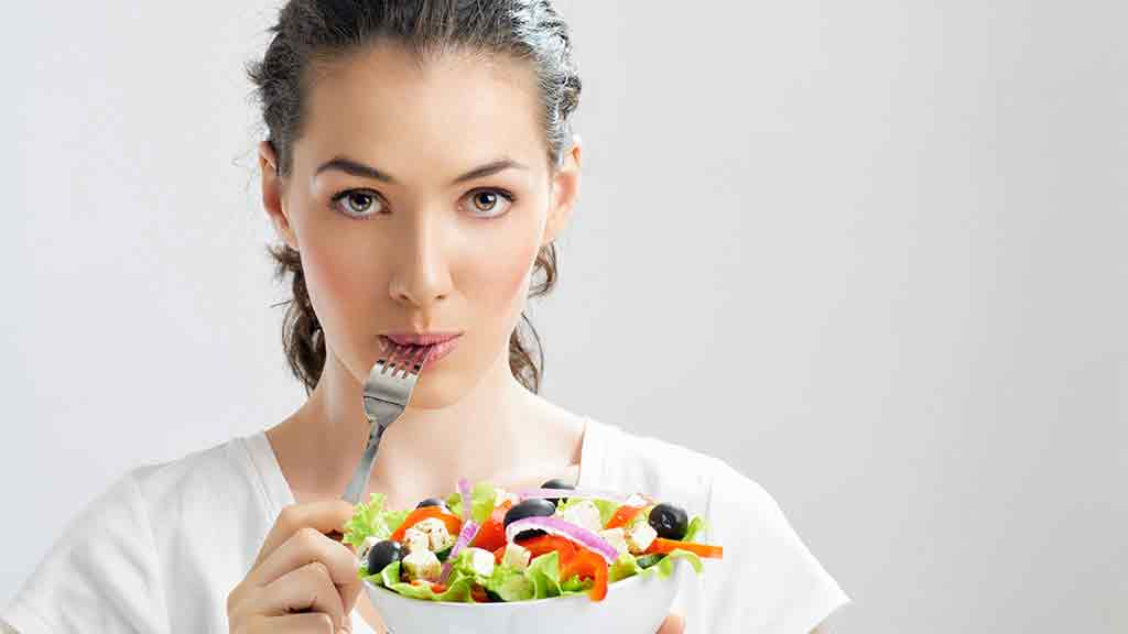 woman with fork in mouth eating salad